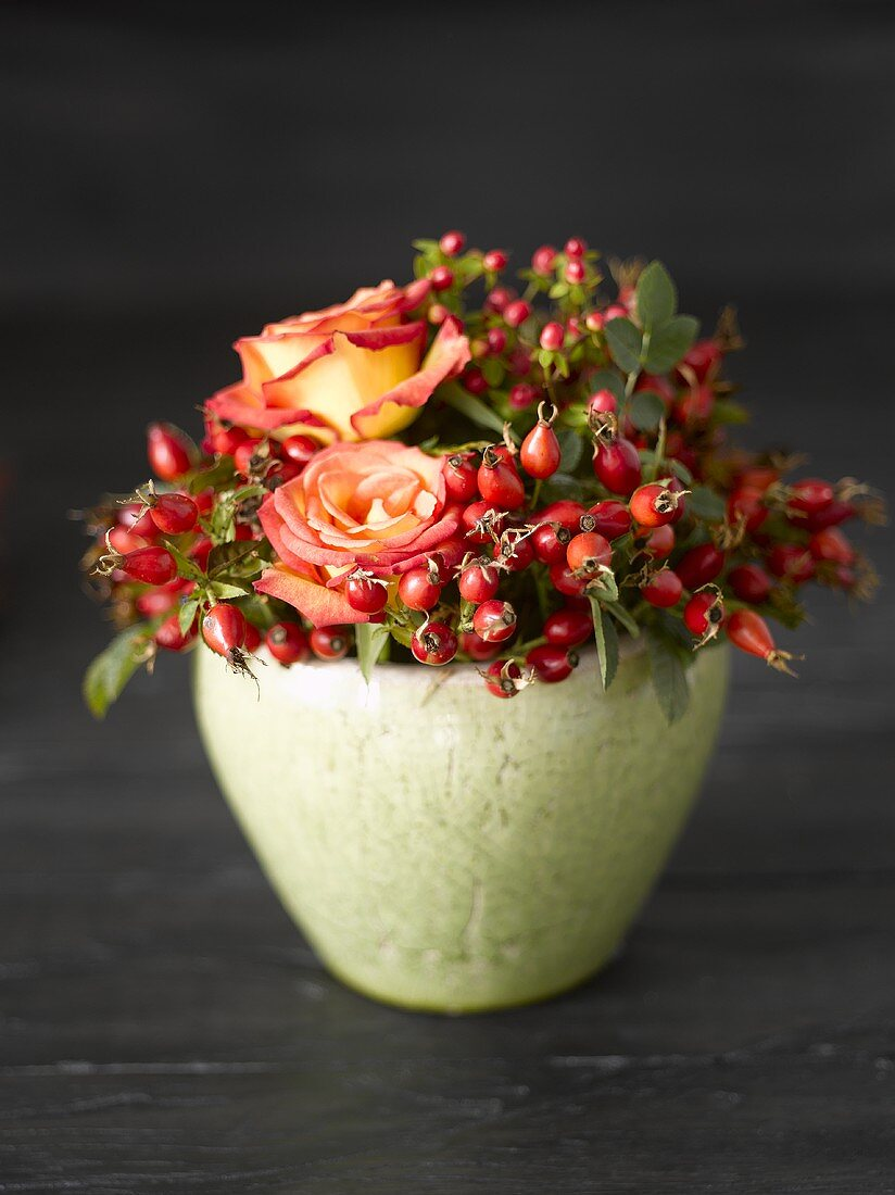 Arrangement of rose hips and roses in green pot