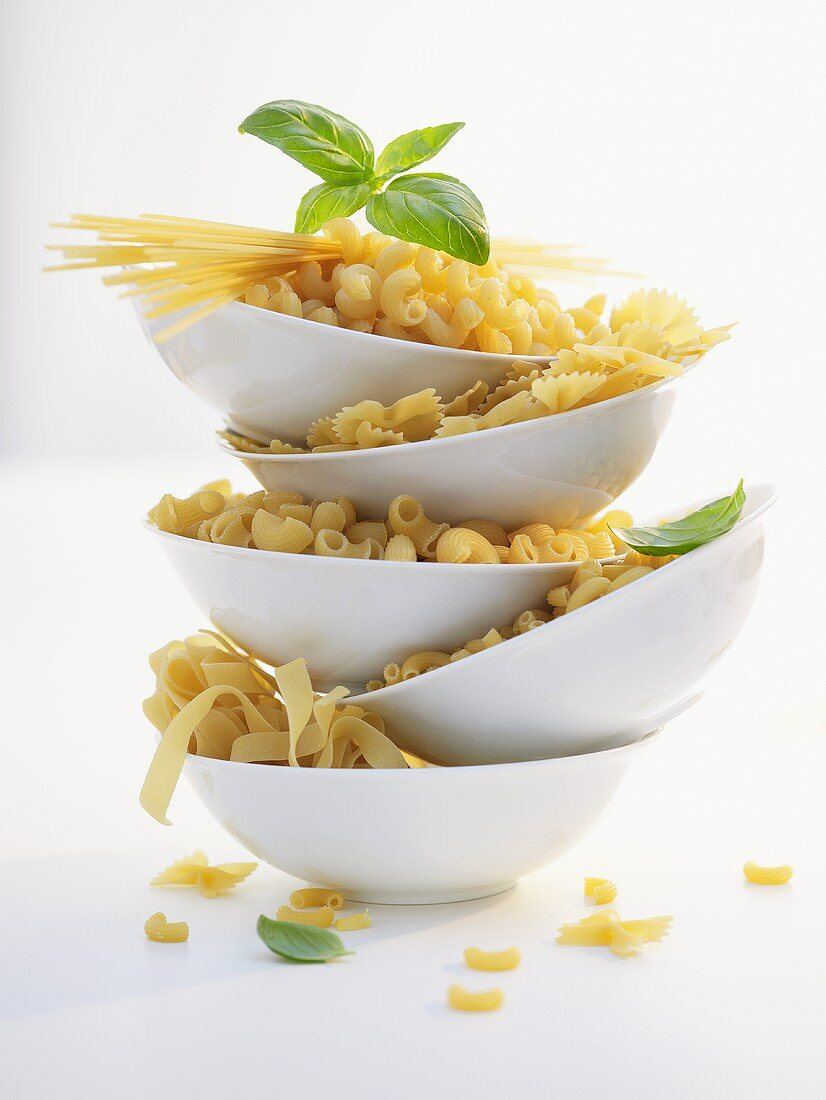 Various types of pasta in five dishes, basil leaves