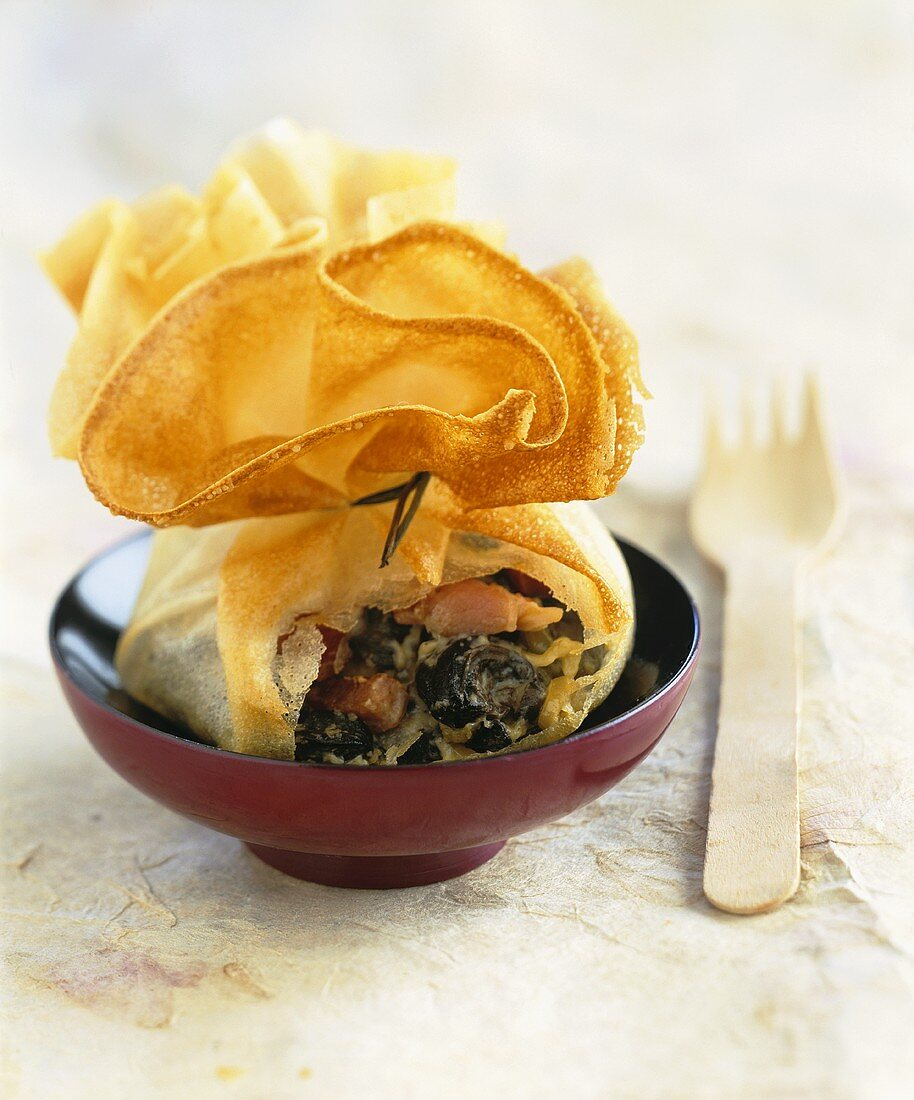 Brik pastry purse with snail and diced bacon filling
