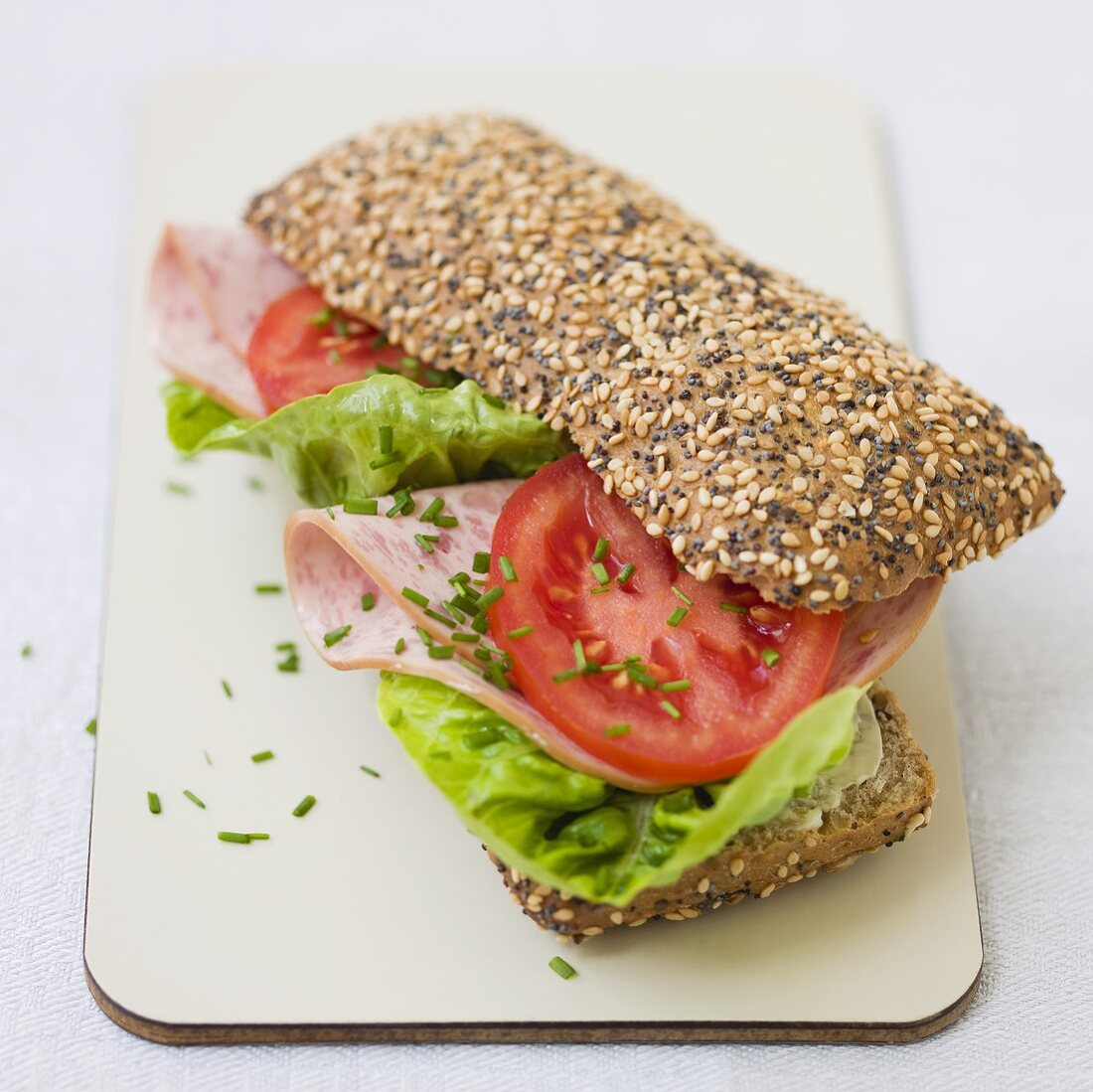 Sliced sausage, lettuce and tomato in wholemeal roll