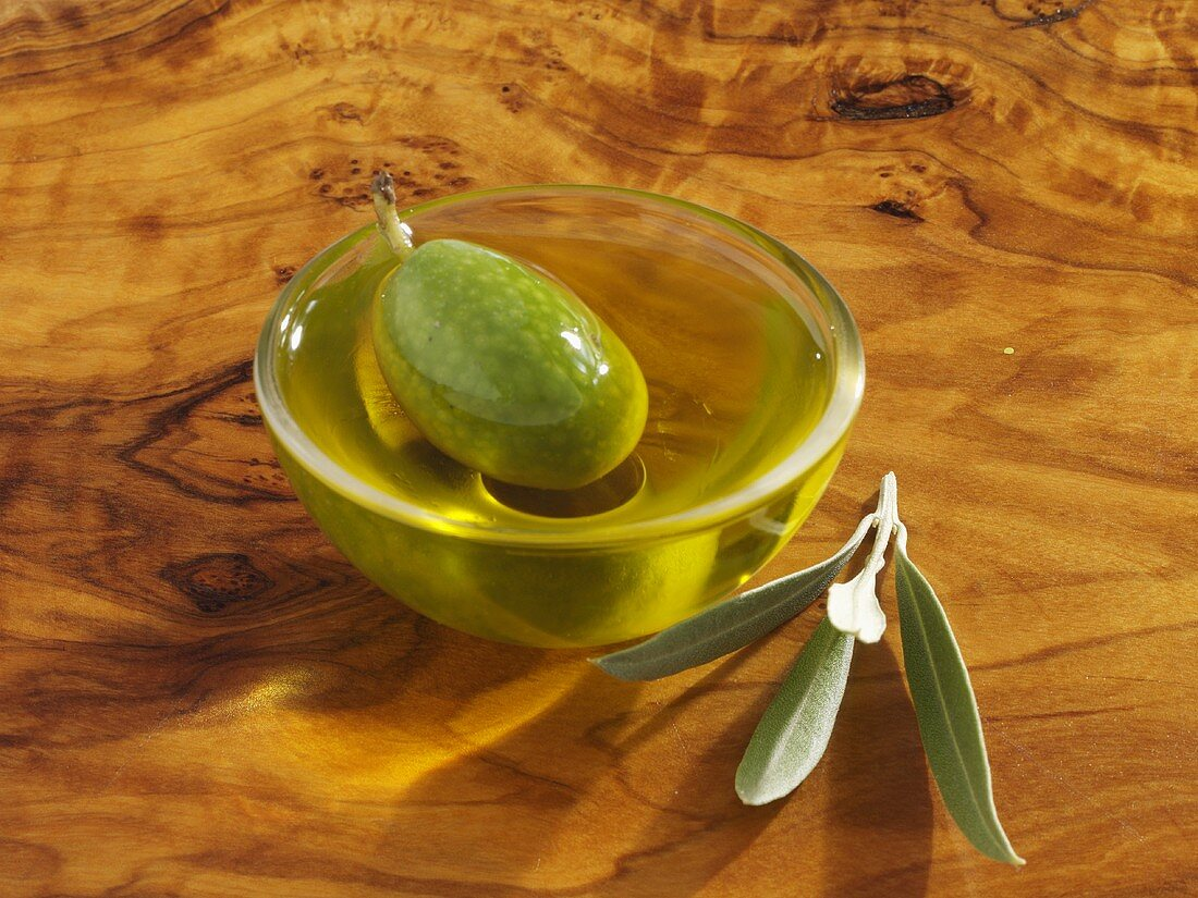 A green olive in a small dish of olive oil, olive leaves