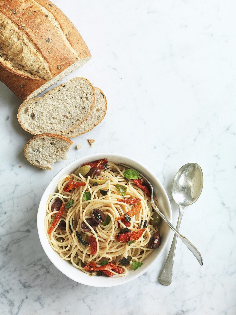 Spaghetti with olives, dried tomatoes and basil
