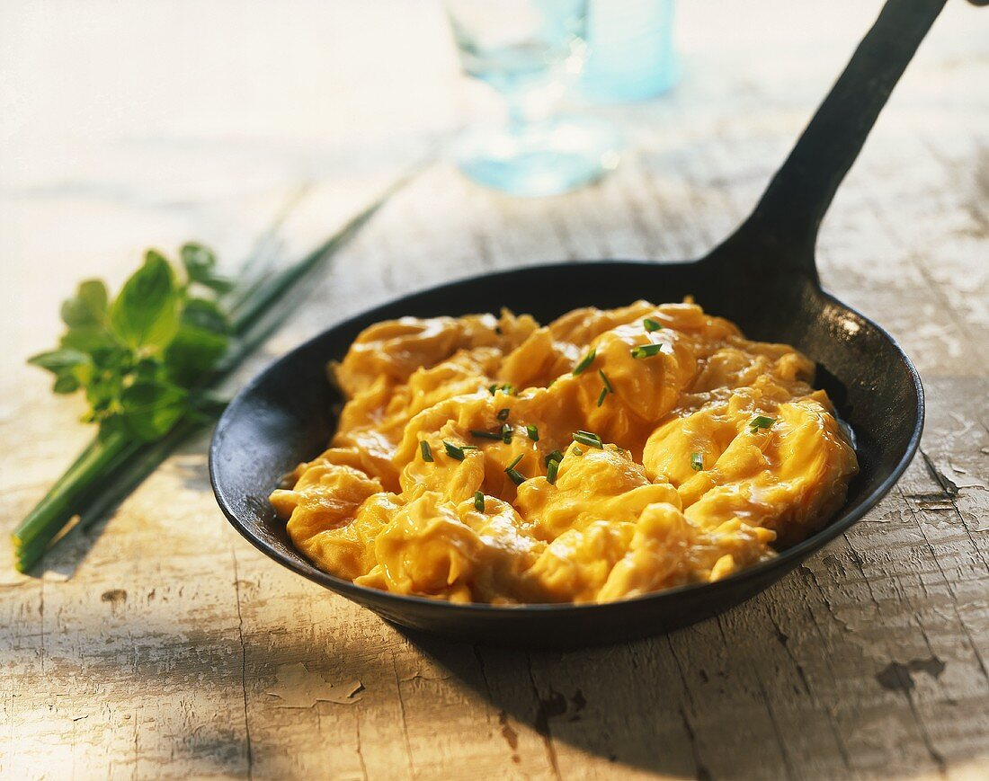 Scrambled egg with chives in cast-iron frying pan