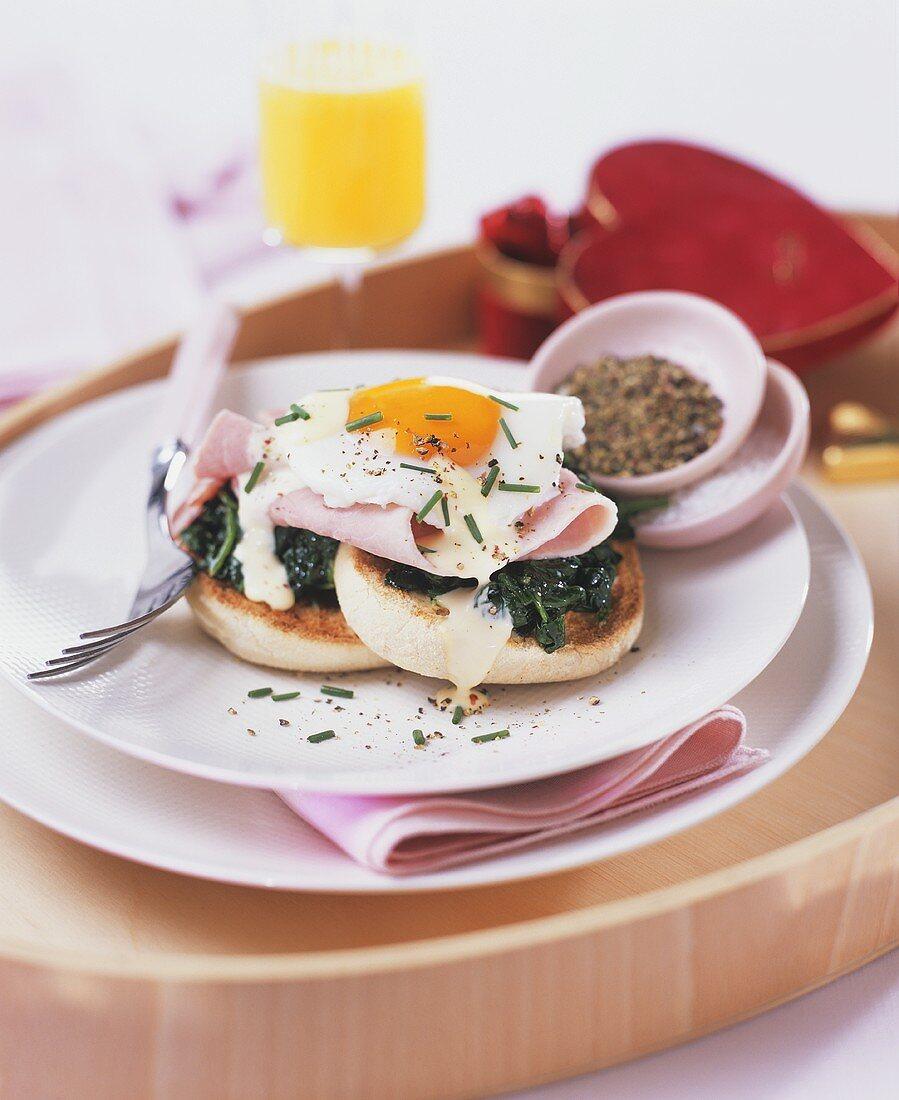 English muffin topped with spinach, ham and fried egg