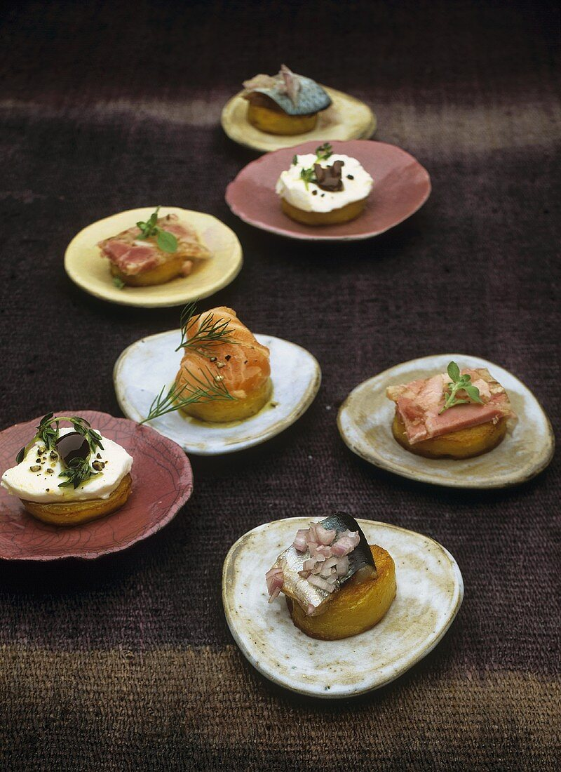Potato canapes with meat in aspic, salmon, herring and goat's cheese