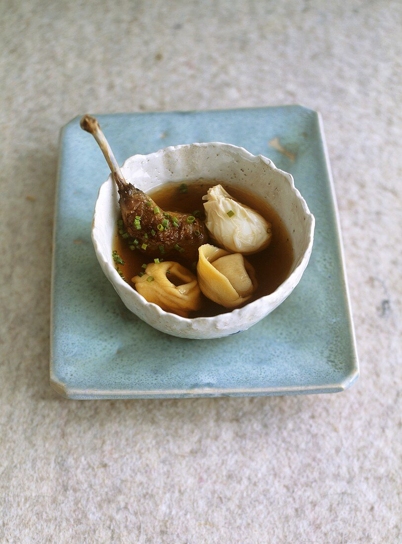 Pigeon consommé with poached quail's egg, tortellini and pigeon leg