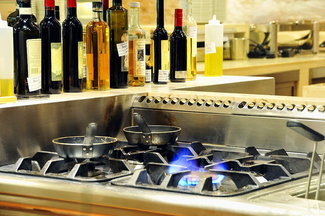 Two pans on a gas hob with dressings in the background
