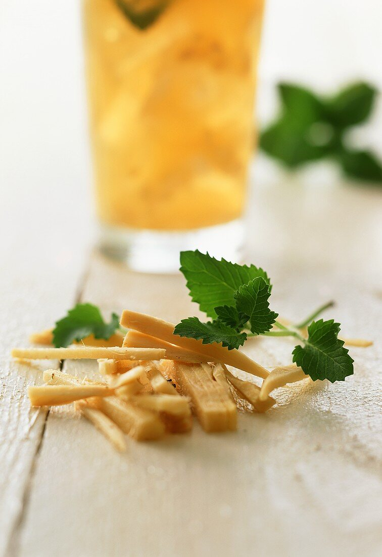 Fresh ginger with a lemon and ginger drink in the background