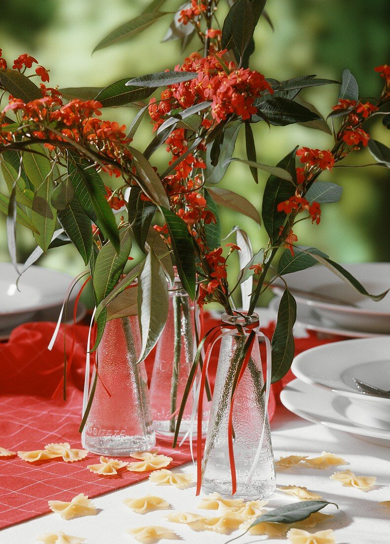 A festively laid table decorated with flowers and pasta