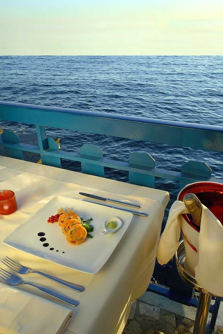 A table with salmon rolls on a balcony overlooking the sea