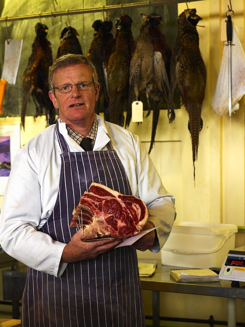 A butcher holding beef ribs in his hands at a Farmer's Market in England