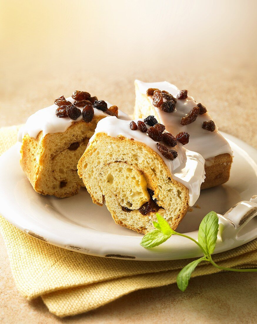Three pieces of yeast dough cake with raisins and icing sugar