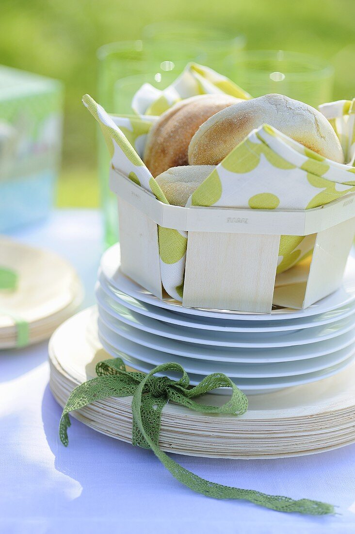 A stack of plates and bread rolls in a basket