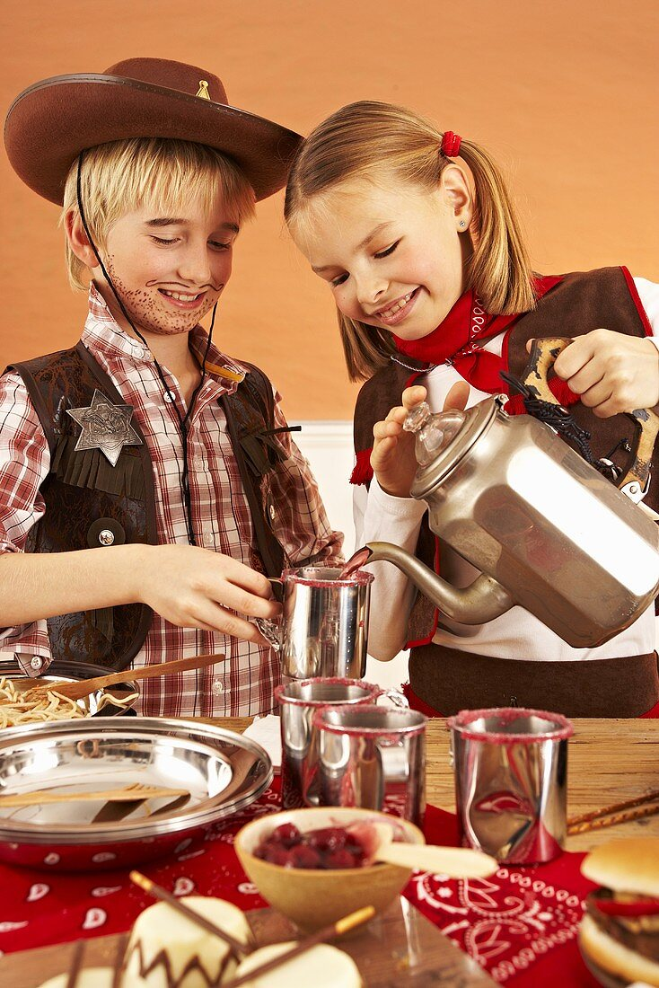 Two children at a party buffet pouring tea