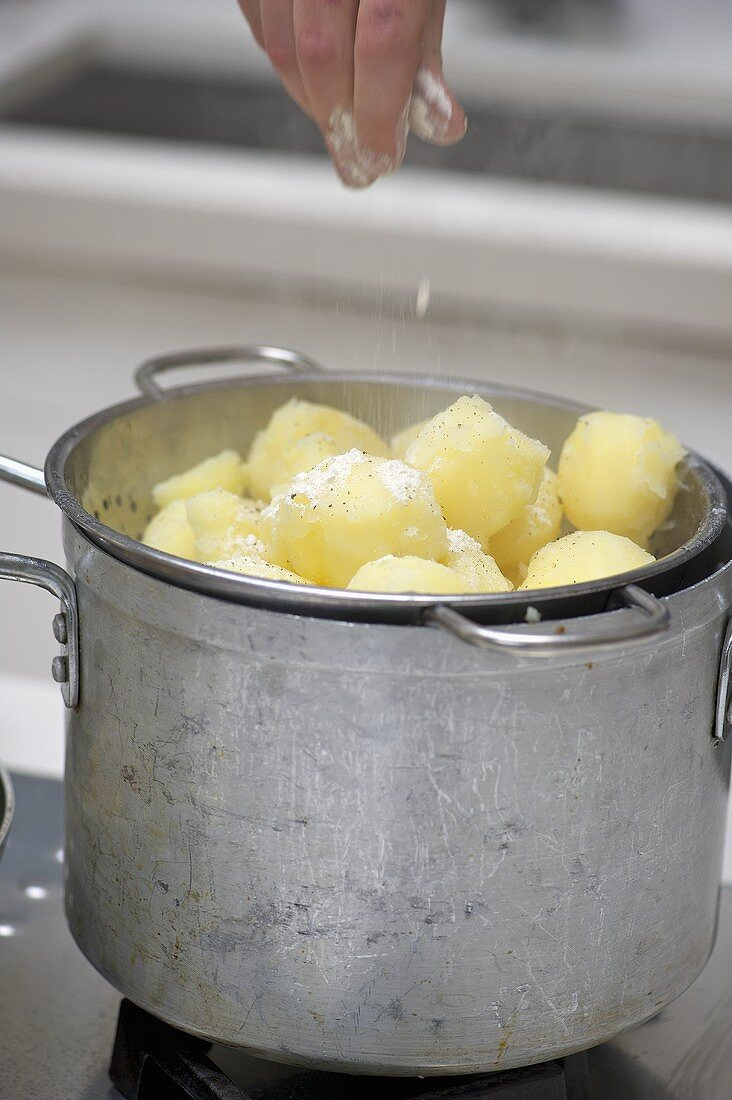 Potatoes being sprinkled with flour