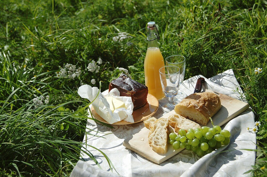 A picnic with ham, butter, ciabatta, grapes and juice