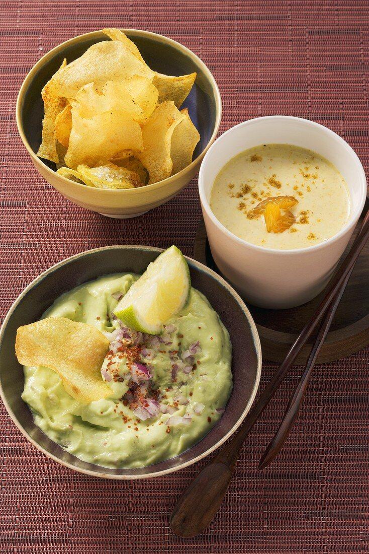 An avocado dip, potato chip and curry sauce with madarins
