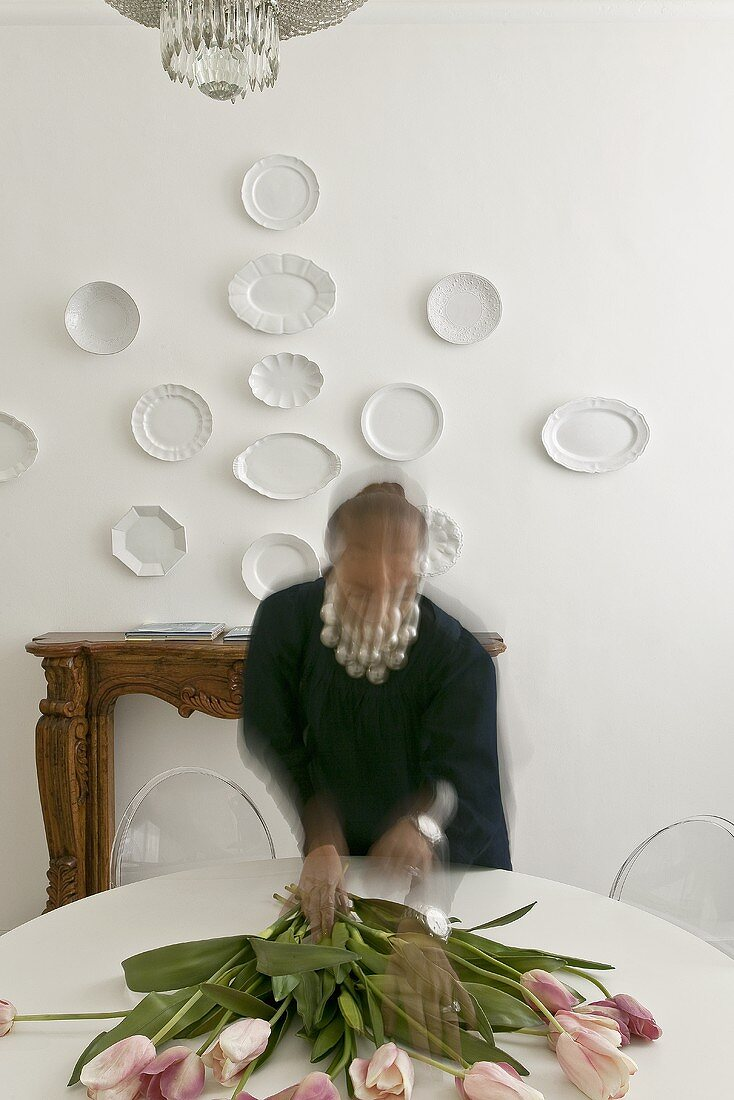 Woman with flowers on a table and white plates on the wall