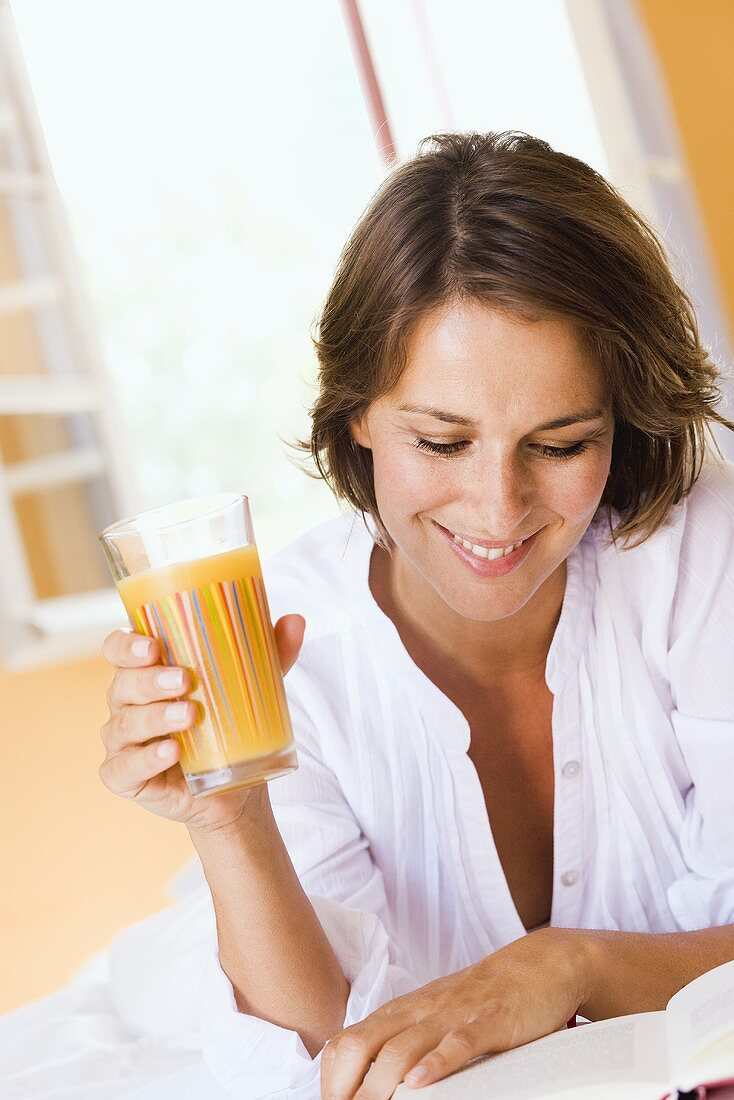 Young woman with orange juice and book