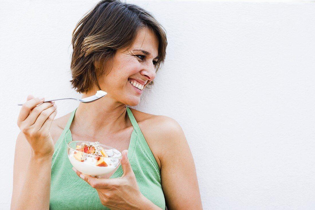 Woman eating muesli with fruit