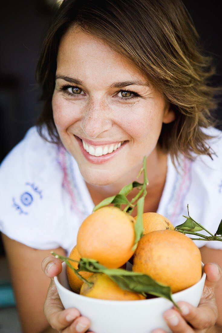 Woman holding a bowl of fresh oranges