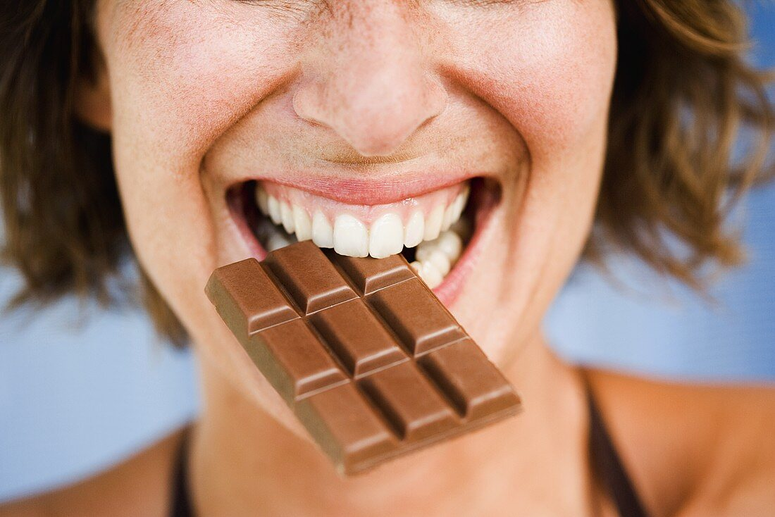 Young woman biting into a chocolate bar