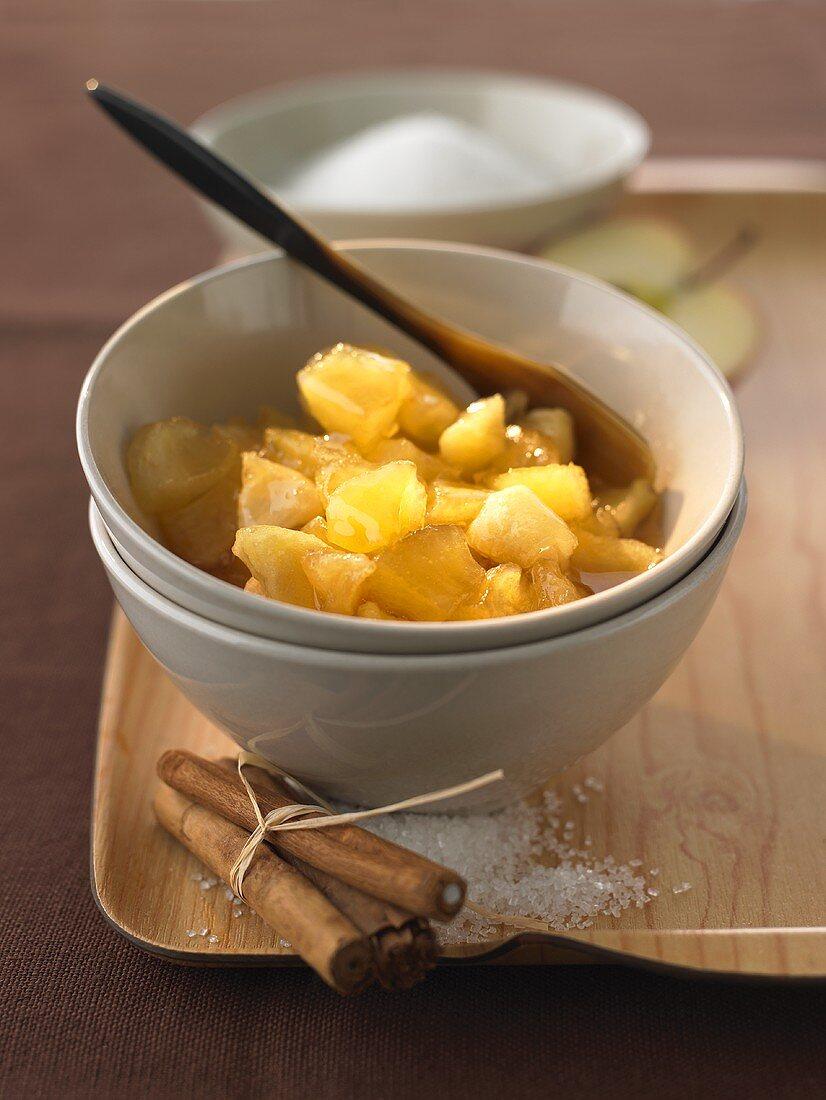 Baked apple jam in bowl, cinnamon sticks, sugar