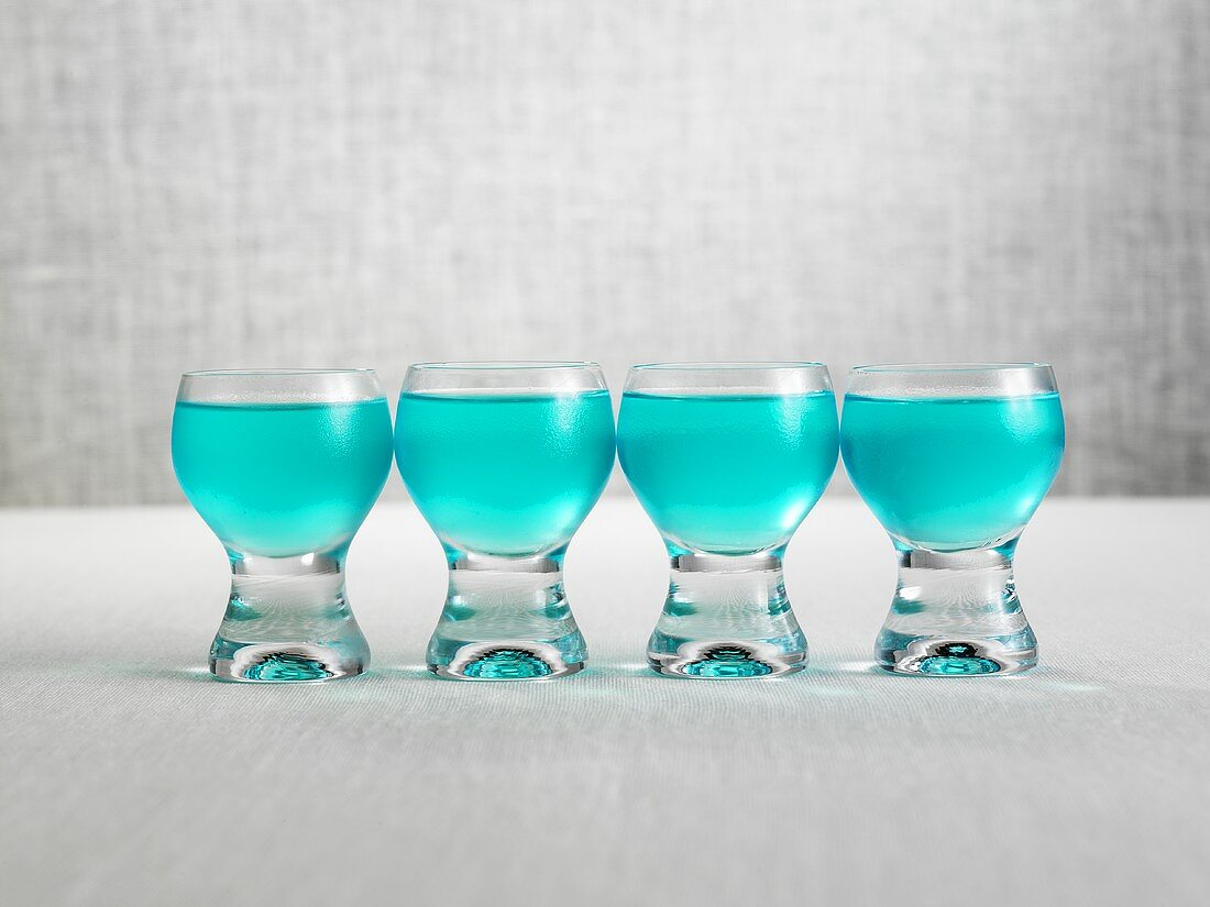 Blue alcopops in four shot glasses