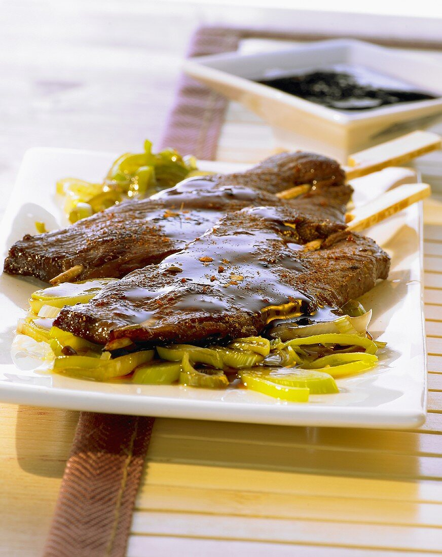 Teriyaki kebabs on a leek medley