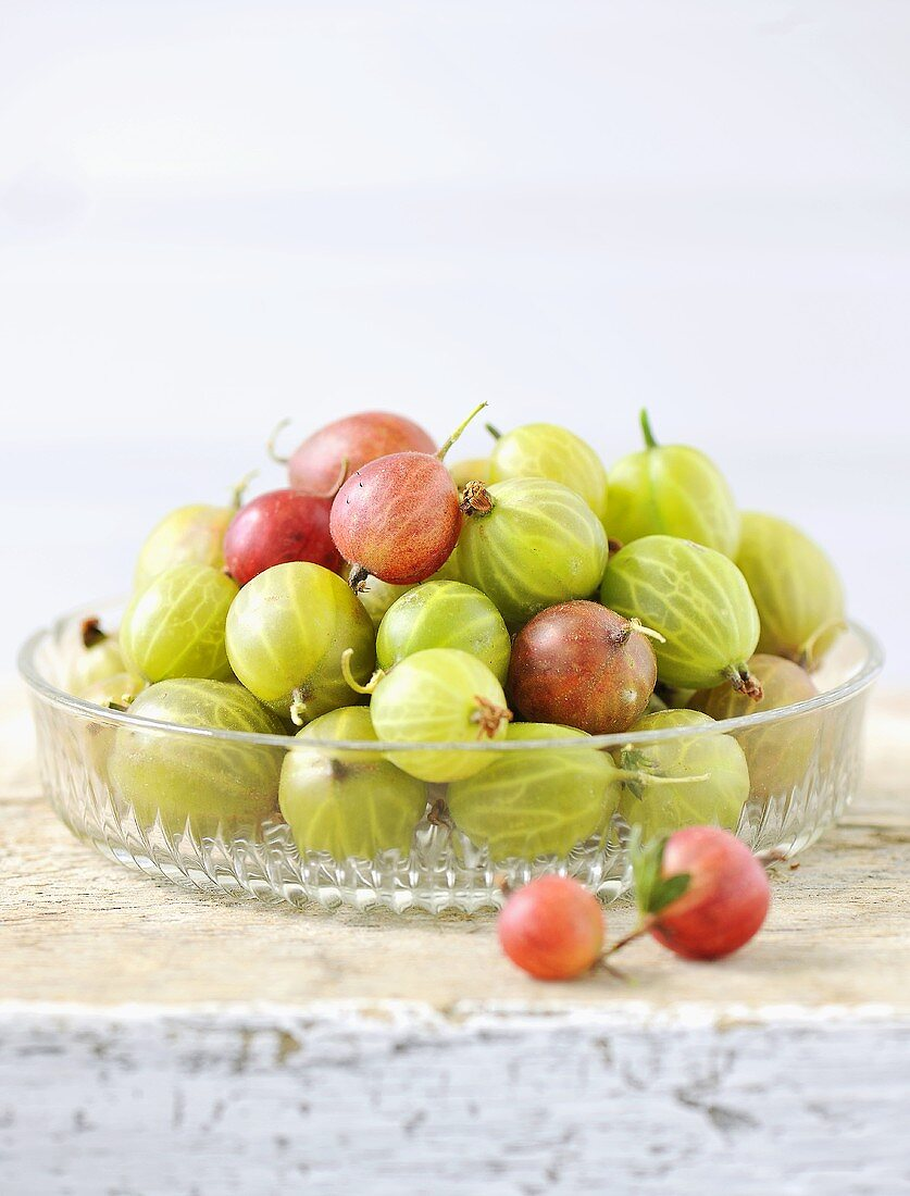 Red and green gooseberries in a glass bowl