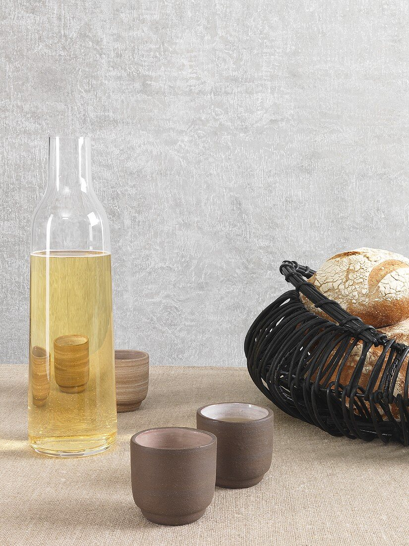 An display featuring a wine carafe with small drinking receptacles and a bread basket