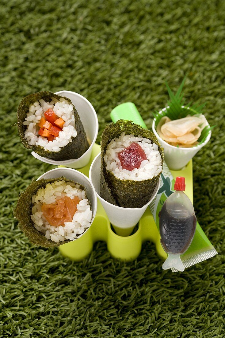 Temaki sushi with salmon, tuna and carrot sticks
