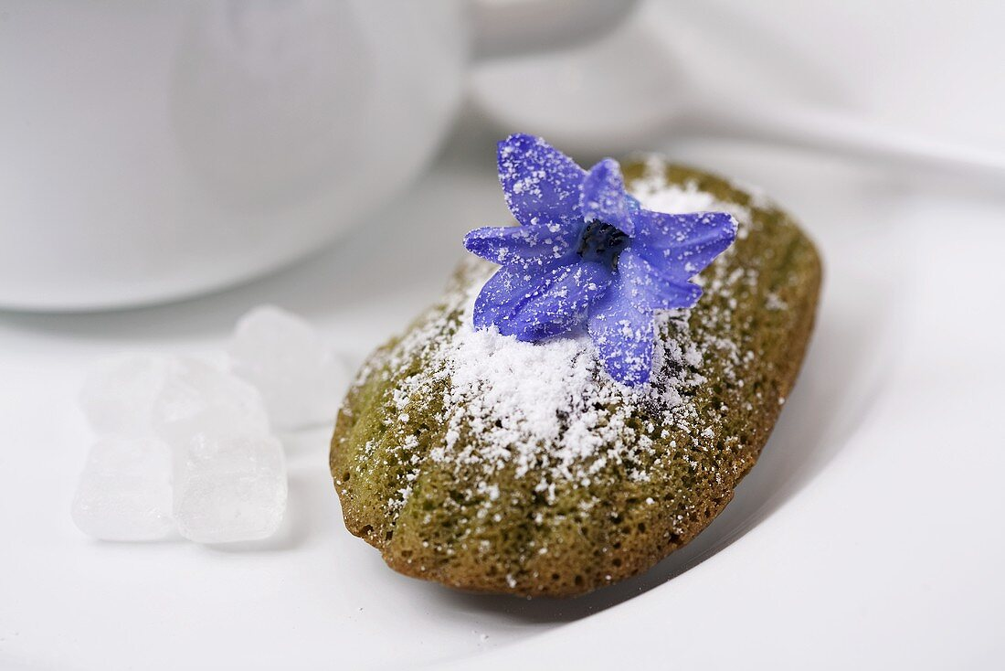 A madeleine with green tea and a hyacinth flower