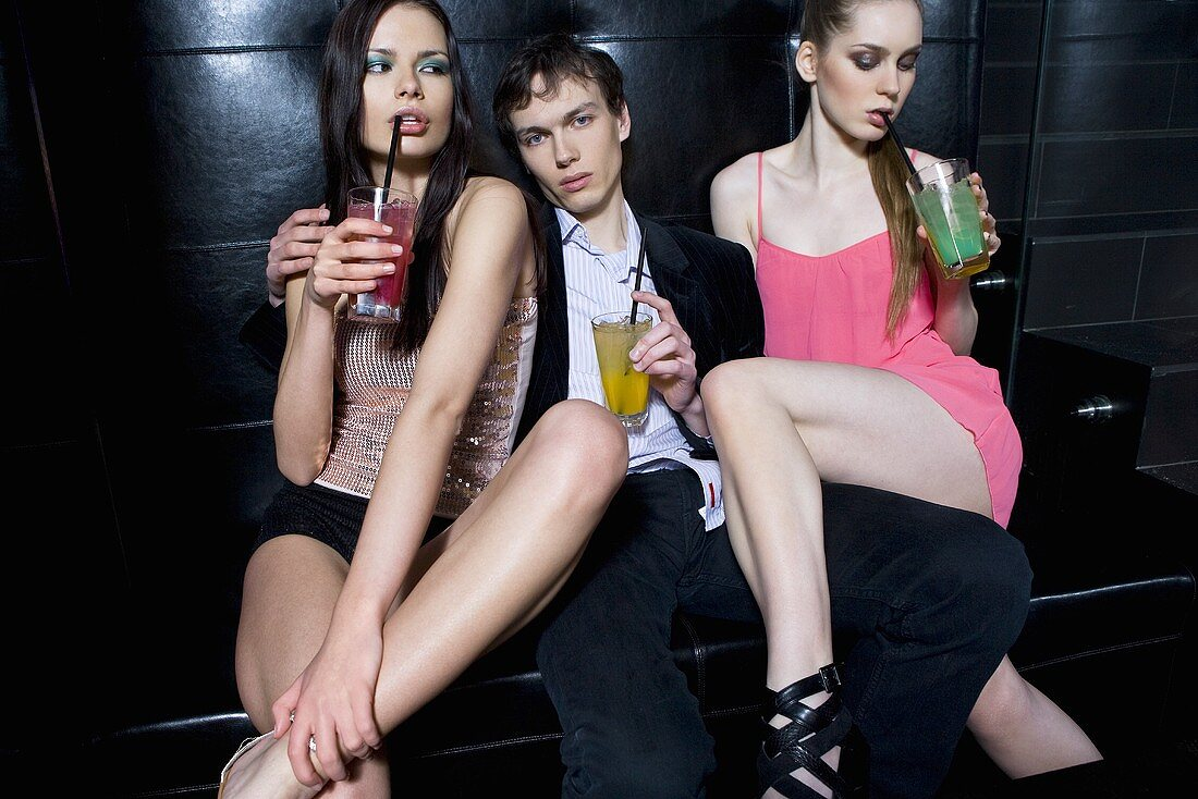 Young people drinking cocktails in a night club