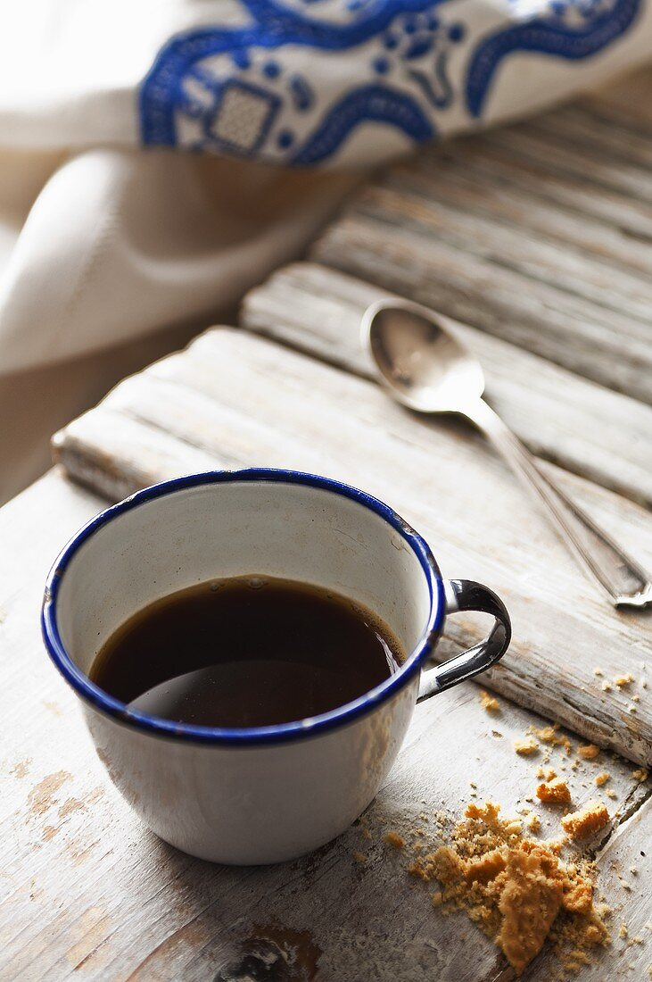 Black coffee in an enamel cup with cake crumbs next to it