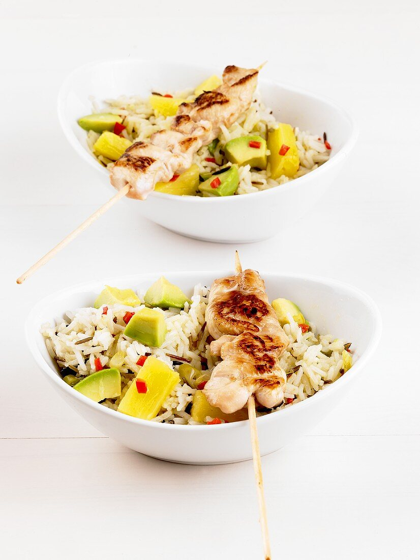 Chicken kebabs on a rice salad with pineapple and avocado