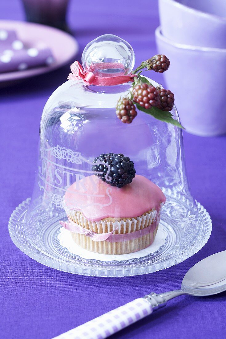 A muffin decorated with pink icing and a blackberry under a cloche