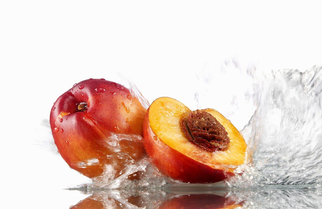 Whole and half nectarine with splashing water