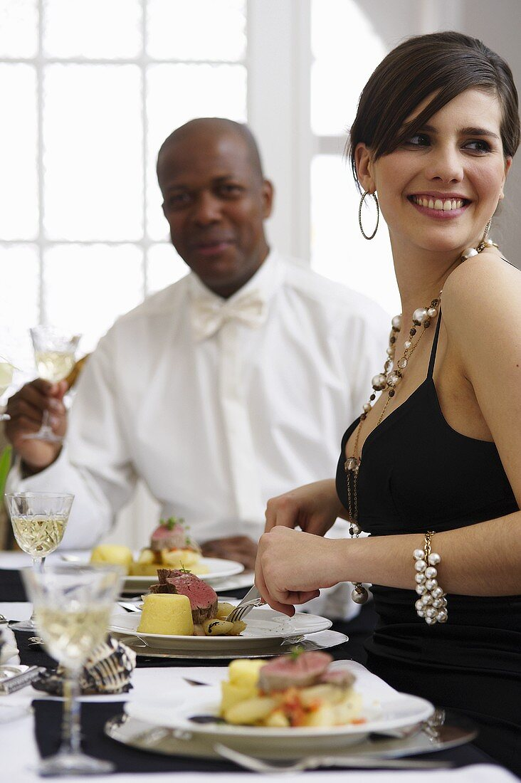 Woman eating veal fillet with semolina timbale at elegant table