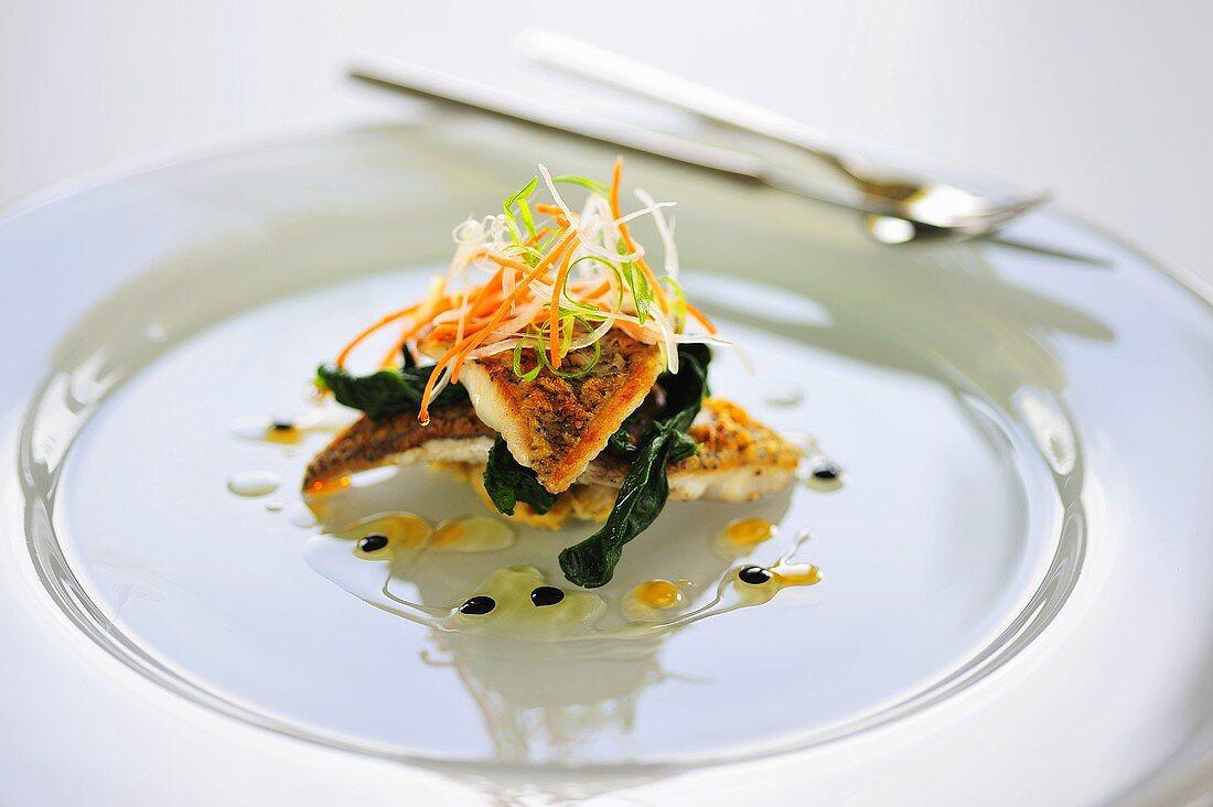 Sea bass fillets on spinach garnished with julienne vegetables