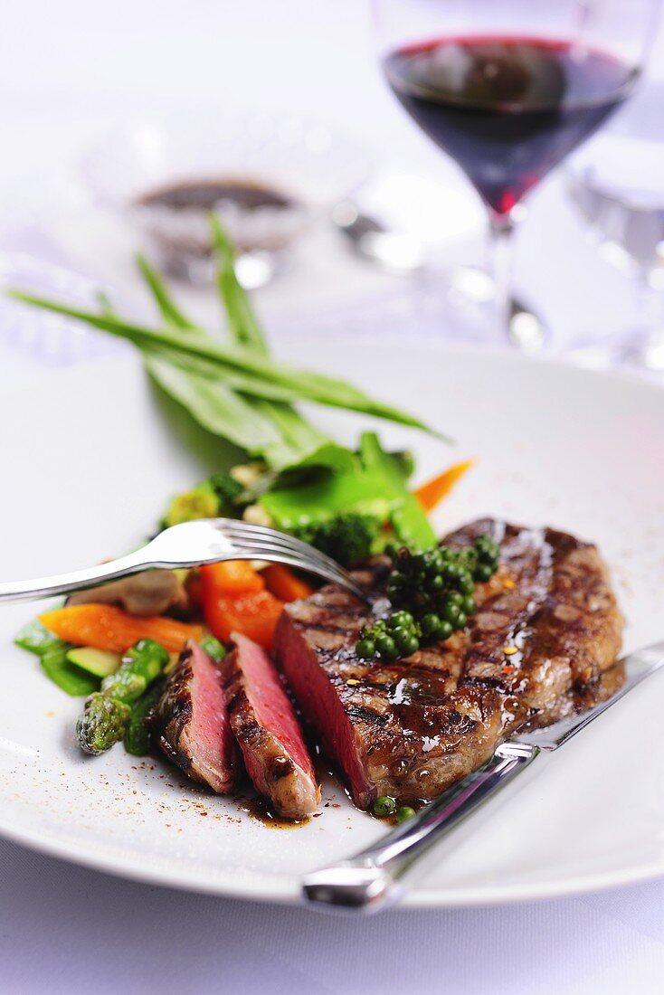 Grilled steak with vegetables, green peppercorns, lemon sauce