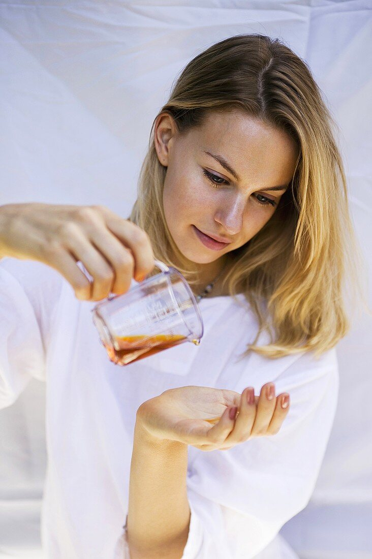Young woman pouring oil into her hand