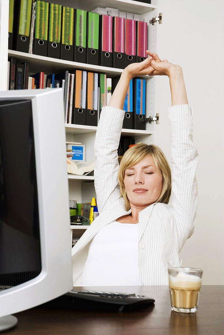 Young businesswoman stretching arms, eyes closed