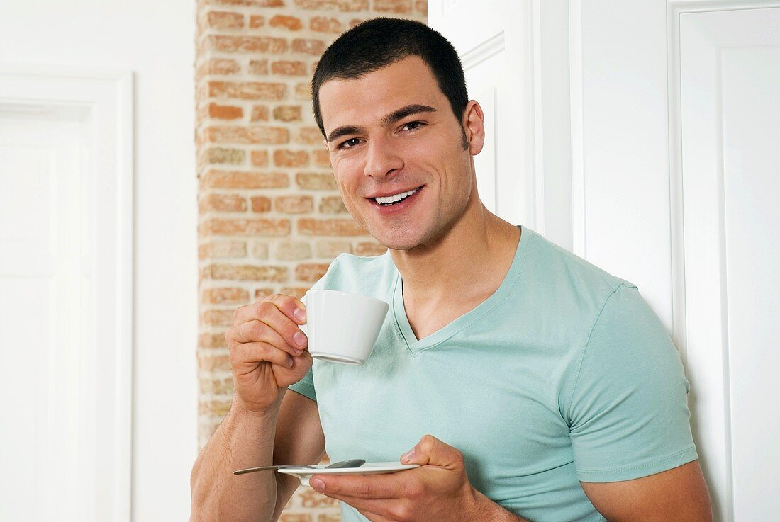 Young man holding a cup of coffee, portrait, close-up