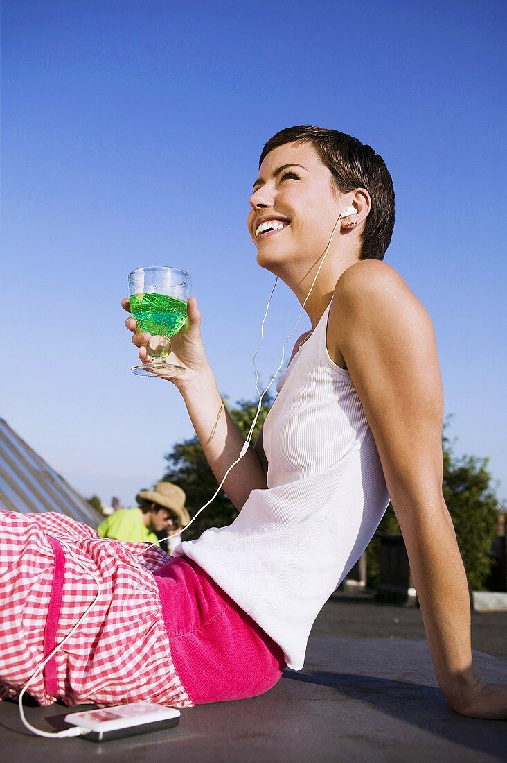 Young woman drinking cocktail & listening to music on headphones