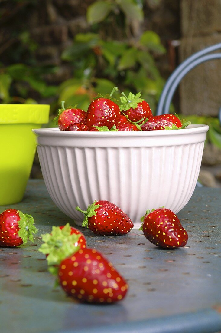Bowl of artificial strawberries on garden table