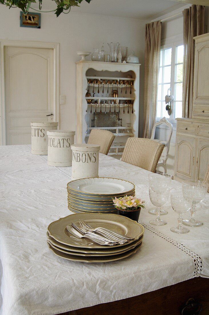 Stacks of plates, cutlery and glasses on dining table