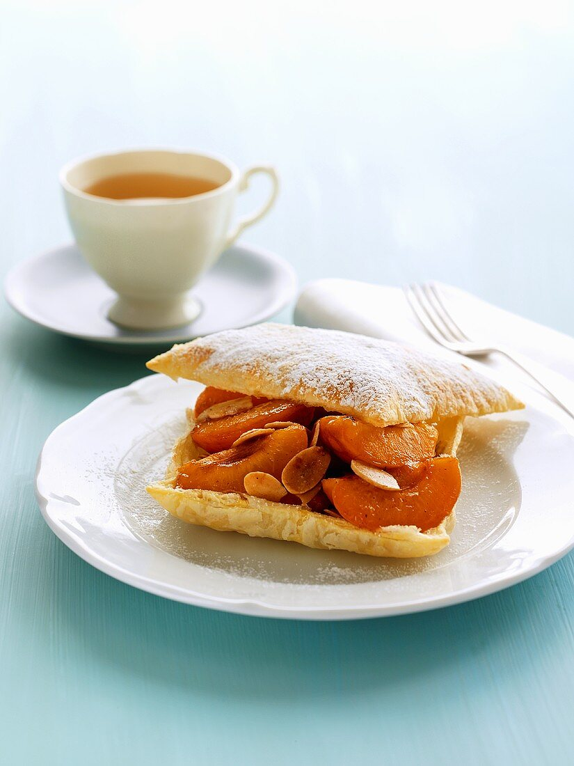 Puff pastry filled with apricots & flaked almonds, cup of tea