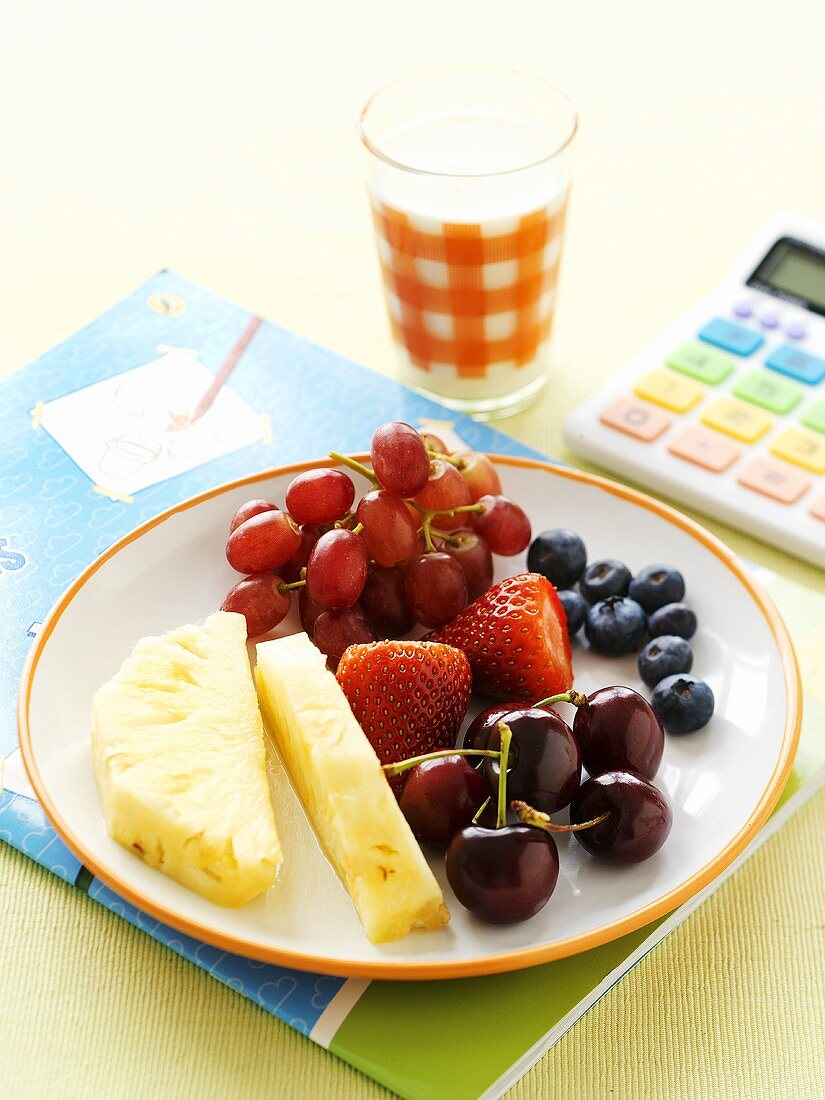 Plate of fruit and glass of milk on exercise book