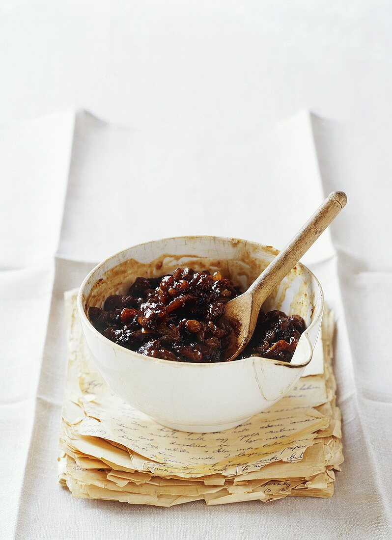 Mincemeat (for mince pies) in small bowl on old recipe book